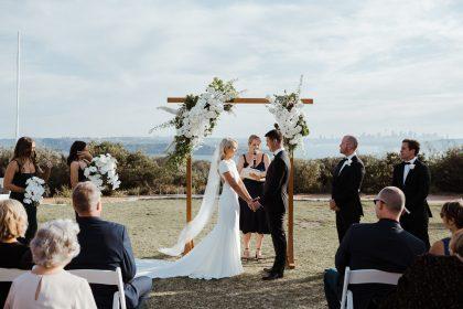 http://A%20bride%20and%20groom%20hold%20hands%20in%20front%20of%20an%20arbour%20in%20an%20outdoor%20wedding%20ceremony.