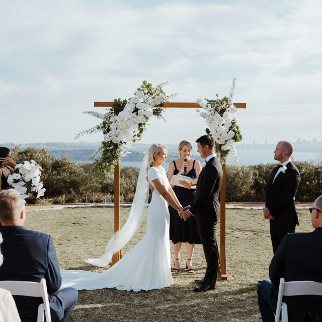 A bride and groom hold hands in front of an arbour in an outdoor wedding ceremony.